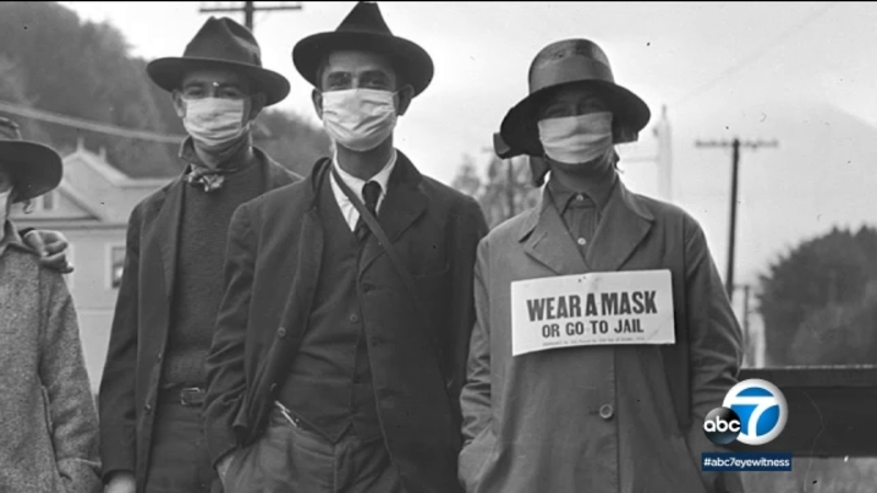 """Citizens walking around in masks, hats, and coats, with a sign that reads """"Wear a Mask or Go to Jail""""."""